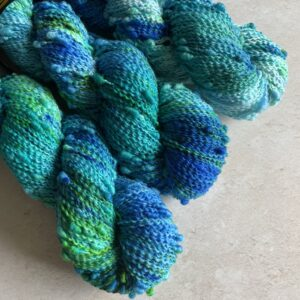 on an off white background are three blue, jade and green variegated skeins of yarns at a diagonal from the top left. The yarn is slightly crimped with regular bobbles. It looks really fun and tactile