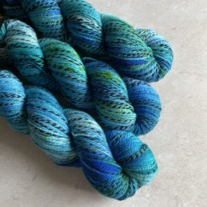 on an off white background are three marbled blue green skeins of yarn on an angle from he top left. The yarn has one strand twisted throughout which moves from silver grey into black and back again.
