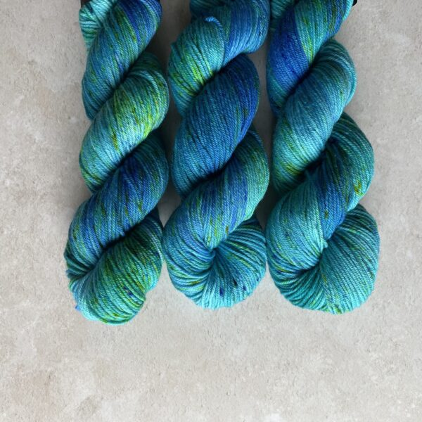 on an off white background are three blue, jade and green variegated skeins of yarn with some bright green speckles. They are placed at the top centre of the image.