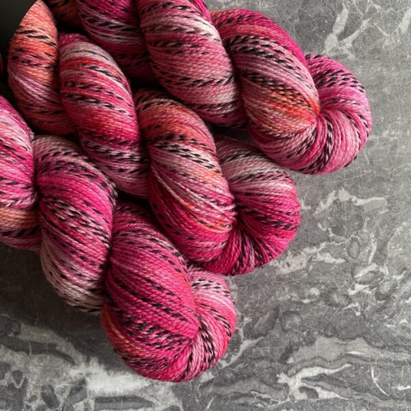 on a grey marble background are three skiens of yarn in various darker and lighter shades of pink and coral. The yarn has one strand twisted throughout which moves from silver grey into black and back again.