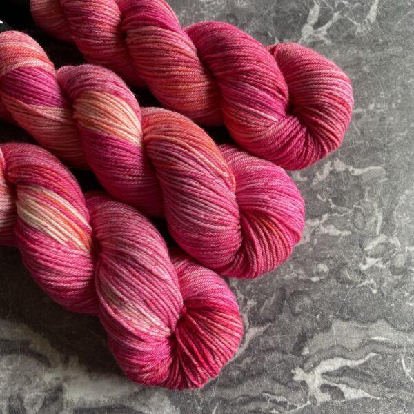 on a grey marble background are three twisted skeins yarn. They are dyed in shades of pink and coral, with darker and lighter areas and varying pink speckles also.