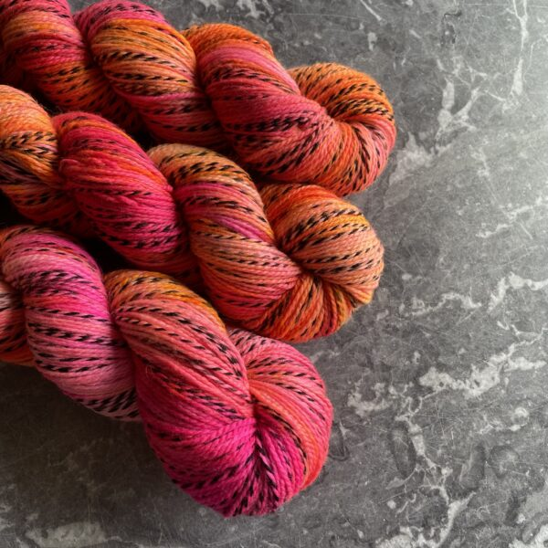 on a grey marble background are three skeins placed at an angle from the top left. Its dyed in shades of neon pink, neon orange and neon yellow with some blending between the colours. The yarn has one strand twisted throughout which moves from silver grey into black and back again.
