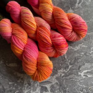 on a grey marble background are three skeins placed at an angle from the top left. Its dyed in shades of neon pink, neon orange and neon yellow with some blending between the colours & a smattering of speckles too.