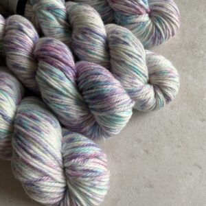 on an off white background are 4 skeins of natural yarn speckled with soft pink, lavender and blue.