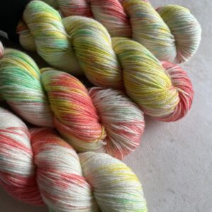 on an off white background are 4 skeins of yarn, with lots of the natural off white showing. The yarn is dyed with flashes of coral, yellow and green. Its light and pretty.