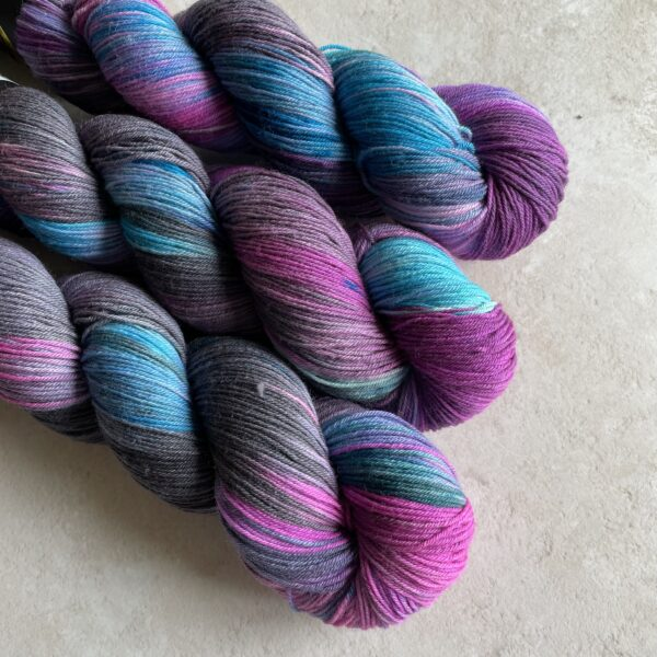 on an off white background are three skeins of yarn placed at an angle from the top left. The yarns are a mix of pinky purple, neon blue and charcoal.