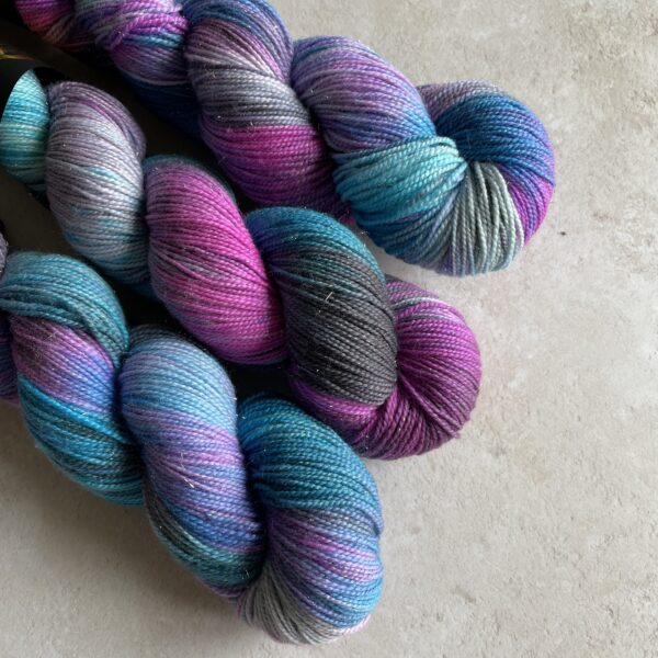 on an off white background are three skeins of variegated yarn in shades of pinky purple, blue and grey/black with lots of blending and some white flashes. There is a subtle sparkle thread running through the yarn.