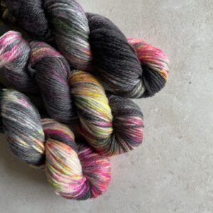 on an off white background are three skiens of plump yarn dyed with random blocks of deep charcoal. the white areas are heavily speckled with hot pink, neon orange and neon yellow.