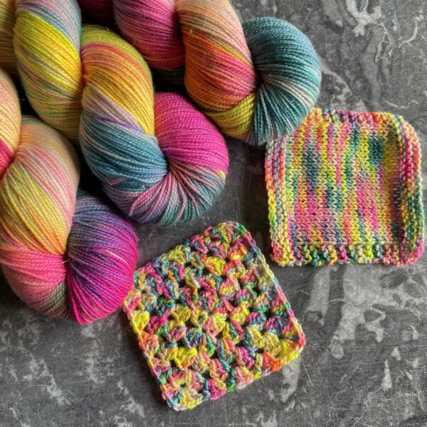 on a grey marble background are 3 sparkley skeins along side knit and crochet swatches. the yarn is neon pink, neon yellow, neon blue with areas of orange and green as the colours mix.