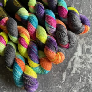 on a grey marble background are 5 variegated skeins placed at an angle from the top left. The yarn has sections of pink, orange, yellow, green, blue, purple and black.