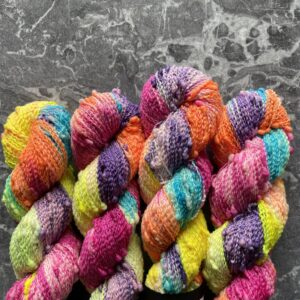on a grey, marble background are four regular repeating skeins of yarn coming from the bottom of the image. They are dyed in soft purple, bright blue, orange yellow, soft green and bright pink sections.. The yarn is slightly crimped with regular bobbles. It looks really fun and tactile