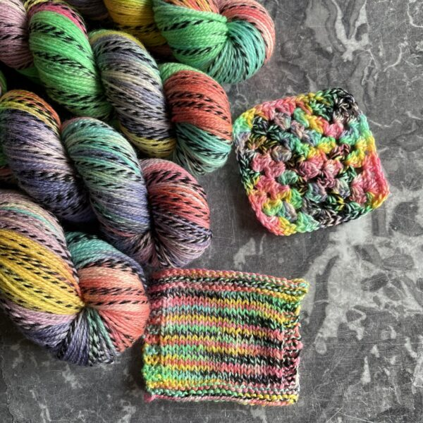 on a grey marble background are 4 skiens of yarn with knit and crochet swatches. The yarn is dyed in variegated blocks of pastel colours in a rainbow. The yarn has one strand twisted throughout which moves from silver grey into black and back again.