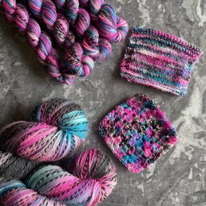 on a grey marble background are 4 mini skeins and two full sized skeins alongside knit & crochet swatches. its dyed in variegated shades of pink, blue and black with flashes of white. The yarn has one strand twisted throughout which moves from silver grey into black and back again.